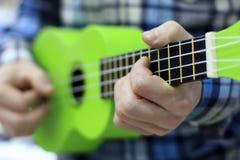 En grabb i en blå rutig skjorta spelar på en grön ukulele royaltyfria bilder