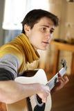 En grabb i en gul tröja sjunger en sång som spelar på hans gitarr royaltyfri bild