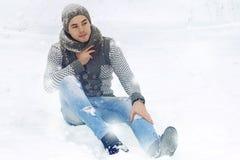 En grabb i en stucken tröja och en hatt sitter på snön arkivfoton