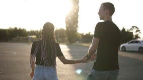 En grabb i en svart T-tröja och en flicka i en svart skjorta med dreadlocks som går vid parkeringsplatsen förbunden förälskelse s arkivfilmer
