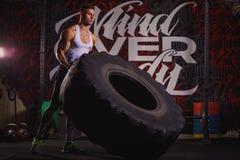 En grabb kastar ett enormt tungt hjul Inomhus i idrottshallen royaltyfria bilder