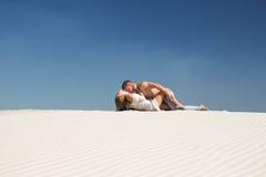 En grabb kysser en kvinna som ligger på sanden royaltyfria bilder