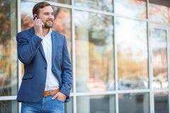 En grabb med ett leende talar på telefonen mot bakgrunden av en glass byggnad arkivbild