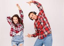 En grabb med en flicka i hörlurar som dansar med deras händer upp på en grå bakgrund arkivfoton