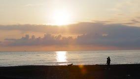 En grabb med en flicka och en hund som går på stranden 003 stock video