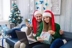 En grabb med en flicka sitter sidan - förbi - sid på en soffa med en bärbar dator royaltyfria foton