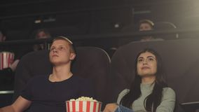En grabb med en flicka som håller ögonen på en film i en filmbiograf, en grabb, frågar att vara tystare arkivfilmer
