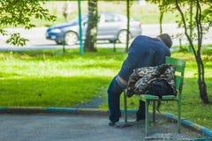 En grabb med en flicka som utomhus sover på en bänk royaltyfri bild