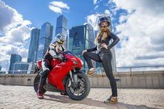 En grabb och den sexiga flickan i en dräkt med en motorcykelsport cyklar Fotografering för Bildbyråer