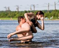 En grabb och en flicka tycker om att plaska omkring i laken Royaltyfri Foto