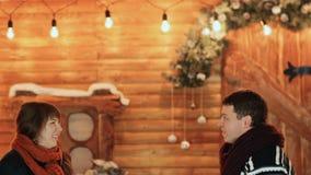 En grabb och en konstgjord snö för flickakast mot bakgrunden av ett sagahus Tema för jul och för nytt år stock video