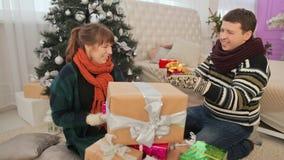 En grabb och flickor tar gåvor ut ur en hög av gåvor och öppnar upp dem som bakgrund är kan det använda julillustrationtemat lager videofilmer