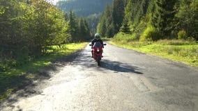 En grabb på en motorcykel Den unga stiliga grabben rider en motorcykel på en bergväg arkivfilmer