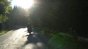 En grabb på en motorcykel Den unga stiliga grabben rider en motorcykel på en bergväg lager videofilmer