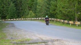 En grabb på en motorcykel Den unga stiliga grabben rider en motorcykel på en bergväg stock video