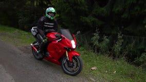 En grabb på en motorcykel Den unga stiliga grabben rider en motorcykel på en bergväg Grabben sitter på hans motorcykel arkivfilmer