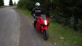 En grabb på en motorcykel Den unga stiliga grabben rider en motorcykel på en bergväg Grabben sitter på hans motorcykel lager videofilmer