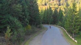 En grabb på en motorcykel Den unga stiliga grabben rider en motorcykel på en bergväg Skjuta från quadcopteren lager videofilmer