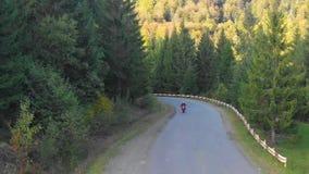 En grabb på en motorcykel Den unga stiliga grabben rider en motorcykel på en bergväg Skjuta från quadcopteren arkivfilmer