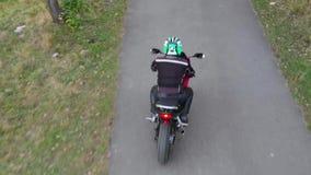 En grabb på en motorcykel Den unga stiliga grabben rider en motorcykel på en bergväg Skjuta från quadcopteren stock video