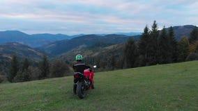 En grabb på en motorcykel Den unga stiliga grabben rider en motorcykel på en bergväg Grabben står nära hans motorcykel och stock video