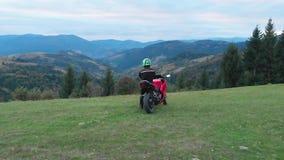 En grabb på en motorcykel Den unga stiliga grabben rider en motorcykel på en bergväg Grabben står nära hans motorcykel och lager videofilmer