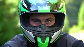 En grabb på en motorcykel Ung stilig grabb med hans motorcykel i bergen Grabben ser kameran close stock video