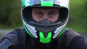 En grabb på en motorcykel Ung stilig grabb med hans motorcykel i bergen Grabben ser kameran close arkivfilmer