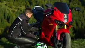 En grabb på en motorcykel Ung stilig grabb med hans motorcykel i bergen Grabben sitter nära hans motorcykel stock video