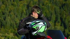 En grabb på en motorcykel Ung stilig grabb med hans motorcykel i bergen Grabben vilar Han dricker vatten stock video