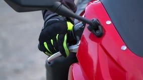 En grabb på en motorcykel Ung stilig grabb med hans motorcykel i bergen Närbild långsam rörelse arkivfilmer