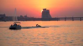 En grabb på en stråle åker skridskor hopp för en fartygsegling längs floden mot bakgrunden av en solnedgång i sommaren som är lån arkivfilmer