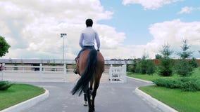 En grabb rider på en häst till arenan arkivfilmer