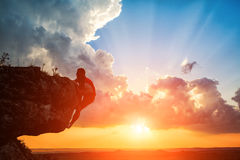 En grabb sitter på en rocknd som ser solnedgång Royaltyfri Bild
