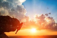 En grabb sitter på en rocknd som ser solnedgång Royaltyfri Fotografi
