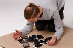 En grabb sitter på hans knä som böjer över en hög av olika splittrade och brutna smartphones Royaltyfri Foto