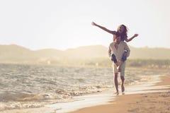 En grabb som bär en flicka på hans baksida, på stranden, utomhus royaltyfria bilder