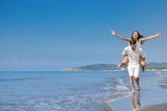 En grabb som bär en flicka på hans baksida, på stranden, utomhus royaltyfri bild