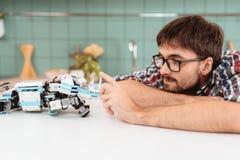 En grabb som poserar med en robot i ett modernt ljust kök Honom som är berörd roboten som ligger bredvid honom Arkivbilder