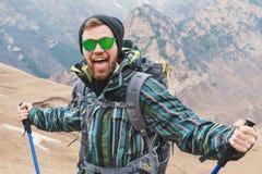 En grabb som ser som en hipster, visar hans tunga och skriker i bergen som ut sträcker hans händer i olikt Fotografering för Bildbyråer