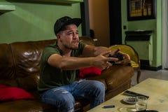 En grabb spelar mycket intensivelly en videospel och röker i den samma tiden royaltyfri fotografi