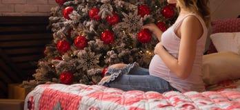 En gravid flicka i en vit T-tröja och jeans sitter på sängen nära trädet för det nya året, en gåva för det nya året arkivfoto