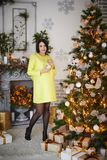 En gravid flicka klär en julgran arkivbild