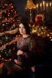 En gravid flicka klär en julgran royaltyfri bild