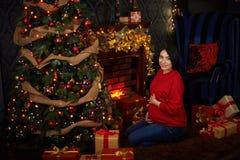 En gravid flicka klär en julgran arkivfoto