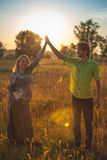 En gravid härlig kvinna med hennes make på naturlandskap som ler och trycker på hennes buk med förälskelse och omsorg Lyckligt fotografering för bildbyråer