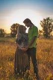 En gravid härlig kvinna med hennes make på naturlandskap som ler och trycker på hennes buk med förälskelse och omsorg Lyckligt Royaltyfri Bild