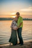 En gravid härlig kvinna med hennes make på stranden för flodbank som ler och trycker på hennes buk med förälskelse och omsorg Lyc Royaltyfri Foto
