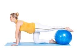 En gravid kvinna gör gymnastik med bollen Arkivfoto