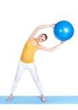 En gravid kvinna gör gymnastik med bollen Arkivfoton